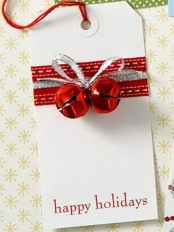 a gift tag with red and silver ribbons and red bells is a very lovely and chic idea for Christmas, add them to the gifts you are giving