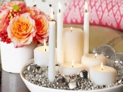 a bowl with silver bells or various sizes, sheer ornaments and candles of various shapes and sizes is a bold and glam Christmas centerpiece