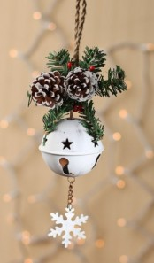 a white star cut bell with a snowflake, fir branches, berries and snowy pinecones is a very chic ornament or just a decoration for your door
