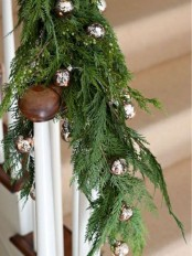 railing decorated with fir branches and silver bells for Christmas – natural and traditional at the same time