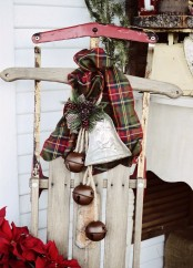 a vintage wooden sledge with a plaid scarf, a porcelain bell ornament and some large brown bells for outdoor decor