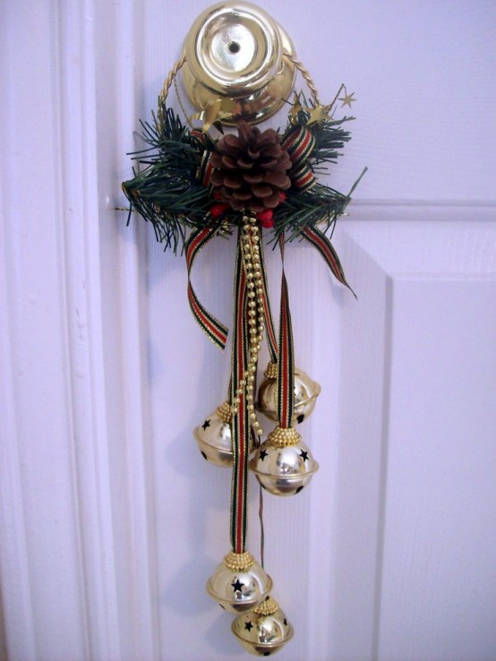 a door accent with bells on striped ribbons, fir branches, a pinecone and a striped bow is bold, glam and colorful