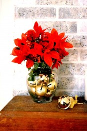 a sheer glass vase with gold bells and faux poinsettia and berries is a lovely and bold Christmas centerpiece