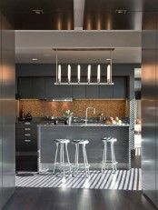 a contemporary grey kitchen with sleek cabinets, a pendant lamp, stools and a large kitchen island plus a cork backsplash