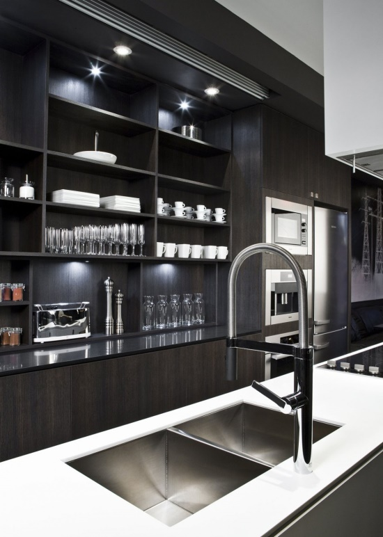 a contemporary dark kitchen with black cabinets, a large white kitchen island, additional lights and stylish faucets