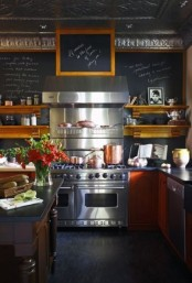 a refined dark kitchen done with a chalkboard wall, amber wooden cabinets, a refined dark dining table and a large cooker,