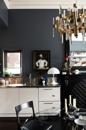 a dark eclectic kitchen with white cabinets, refined chandeliers and artworks, matte grey walls