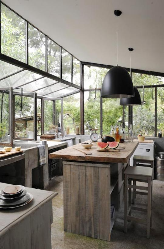 a natural indoor-outdoor kitchen with glazed walls, pendant lamps, rough wooden furniture and lots of concrete
