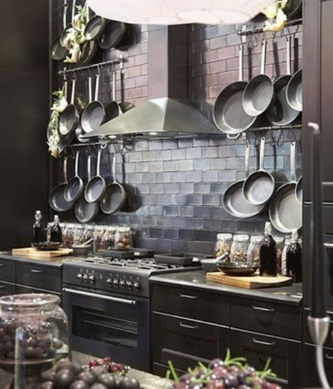 an elegant dark kitchen with tiles, a metal hood, dark cabinets and surfaces, lots of pots hanging on hangers