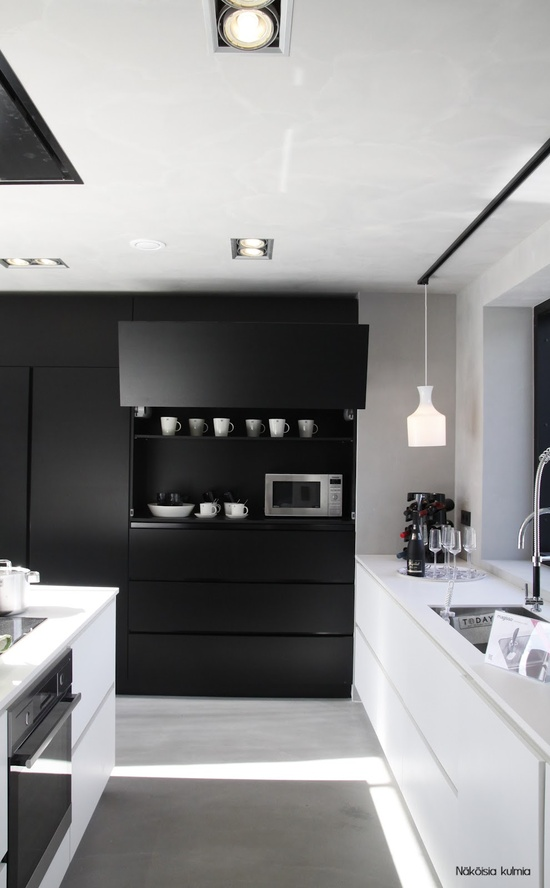 an ultra-minimalist black and white kitchen with all-sleek surfaces is a bold and contrasting idea for a modern person