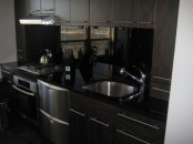 dark furniture and a sleek black backsplash and countertops look very masculine and very outstanding