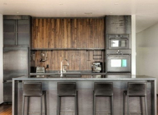 an industrial kitchen with metal cabinets and appliances, a wooden backsplash and cabinets, a metal kitchen island and stools for a masculine feel