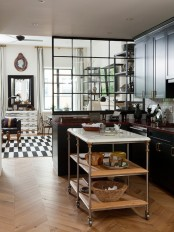 a moody kitchen with dark kitchen cabinets and light-colored wooden countertops and a marble kitchen island
