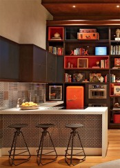 a dark stained wooden kitchen, a white kitchen island with a printed tile backsplash and a catchy backsplash