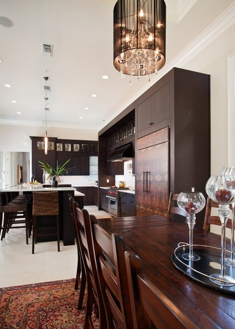 a rich-stained wooden kitchen with white countertops, white backsplashes and lamps and woven stools