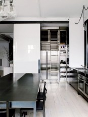 a minimalist black and white kitchen with industrial touches is a chic and very masculine idea with much natural light