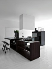 a contrasting minimalist kitchen with a dark kitchen island, a white sleek cabinet, a white hood and a black bar