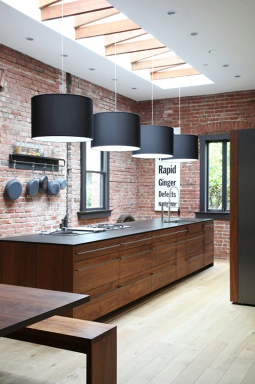 an industrial kitchen with red brick walls, black pendant lamps, a large kitchen island a black countertop