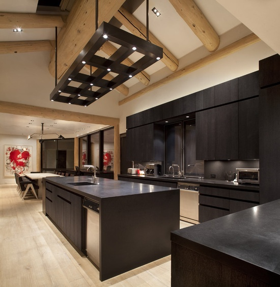 a completely black kitchen with dark cabinets, a sleek backsplash, lights and a lighting frame over the kitchen island