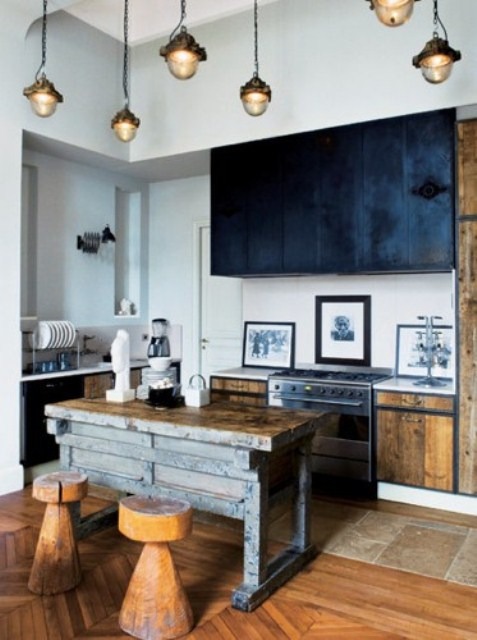 light-colored stained kitchen with black upper cabinets, pendant lamps, an industrial wood and metal kitchen island