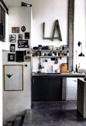 a constrating kitchen with black cabinets, white shelves, rough wooden furniture, a gallery wall and tableware