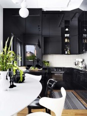 a refined black and white kitchen with dark cabinets, mini white tiles and ultra-modern chairs with sculptural shapes