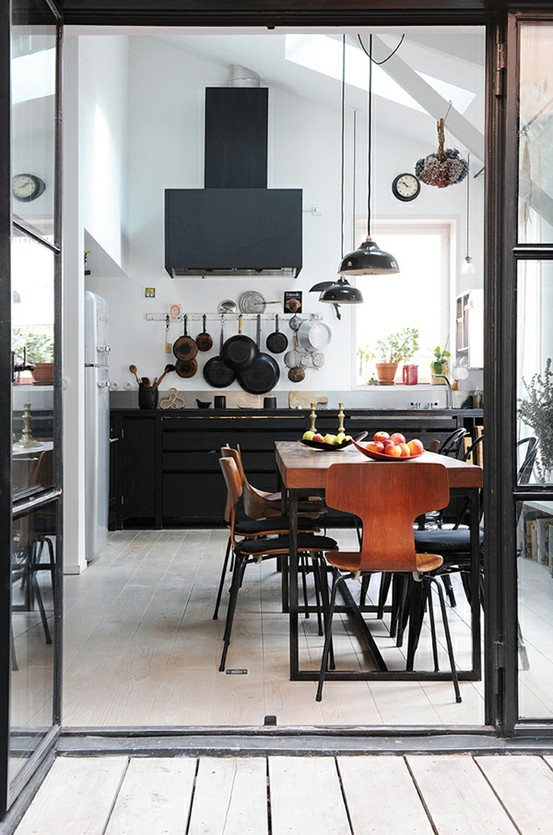 a black metal kitchen with pendant lamps, a black hood, rich-stained wooden dining set is very eye-catchy
