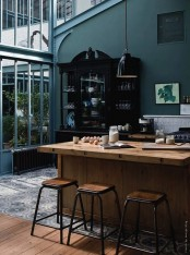 a moody kitchen with dark green walls, refined black furniture, light-colored wooden furniture and black pendant lamps