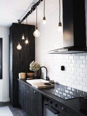 a Nordic black and white kitchen with dark furniture, white subway tiles and hanging bulbs looks bold and chic