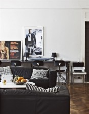 a stylish living room with black upholstered furniture, chairs and pillows, artworks and a desk with chairs by the wall