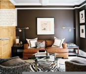 a dark living room with black walls, upholstered and leather furniture, metal lamps, artworks and a glass coffee table