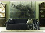 a dark living room with an oversized artwork, dark furniture and elegant armoires with plates on display