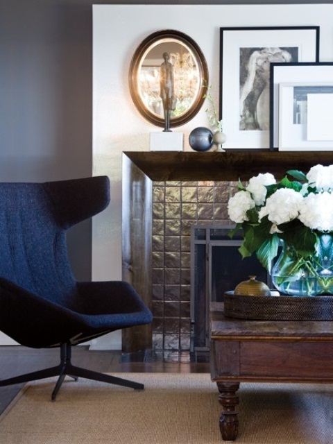 a stylish corner with a black chair, a tile clad fireplace, a wooden coffee table and artworks on the mantel