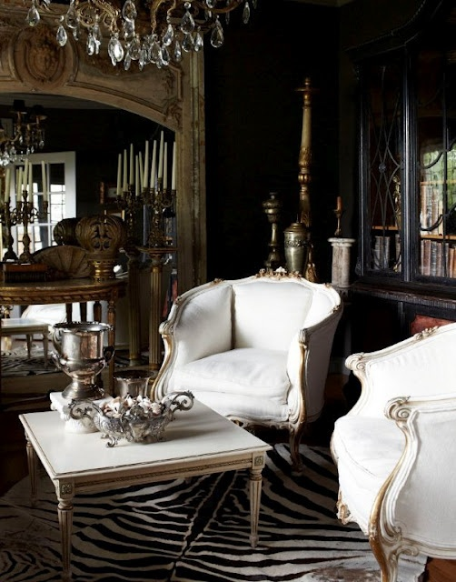 a sophisticated living room with elegant white furniture, an animal skin rug, crystal chandeliers and mirrors