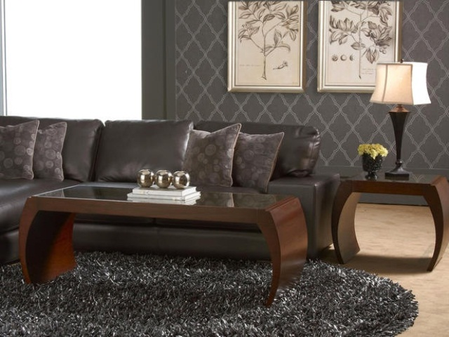 a dark living room with grey furniture, wooden tables, artworks, a fur rug and lamps
