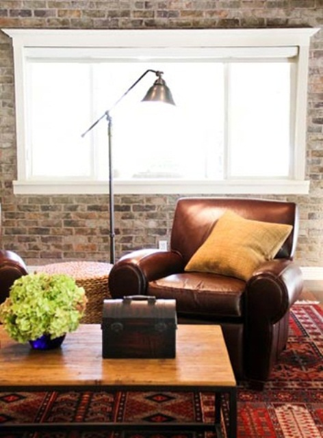 a cozy living room with leather furniture, a wooden coffee table, brick walls, a metal lamp