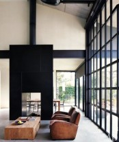 a contemporary living room with a glass wall, a black tile stove, leather chairs and a wooden coffee table