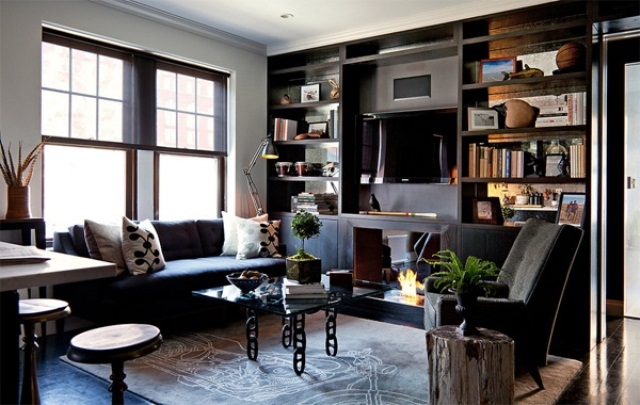 a living room with dark furniture, frames and rugs, glass tables and tree stumps as side tables