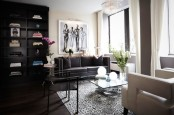 a laconic and refined living room done in neutrals and dark shades, a crystal chandelier, an artwork and neutral curtains