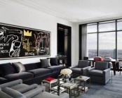 a contemporary masculine living room with dark upholstered furniture, some glass tables, an artwork and a glass wall for views