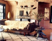 a cozy masculine living room with wooden walls, leather and dark wooden furniture, wooden tables and metal lamps