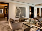 a stylish neutral living room with brown furniture, a glass coffee table and an artwork plus a neutral backdrop