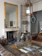 a sophisticated living room with leather furniture, a stone fireplace, refined lamps and glass tables plus a giant mirror