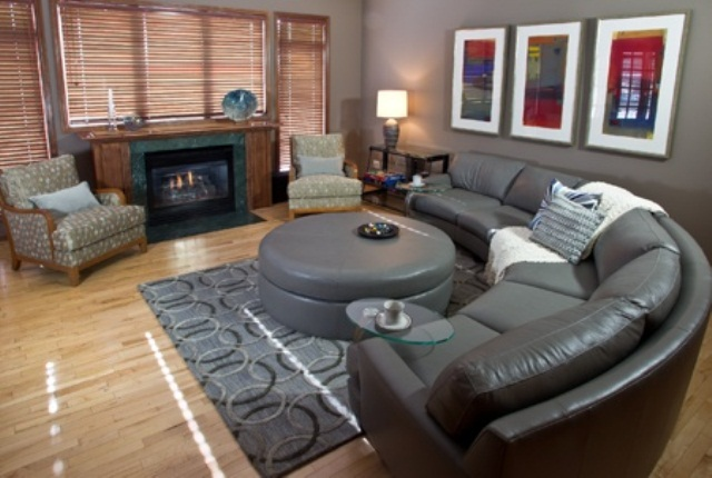a dark living room with leather furniture, artworks, a fireplace and some glass side tables