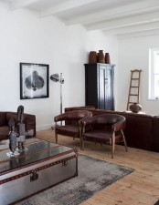 a masculine living space with an industrial feel, brown leather furniture, a wooden cabinet, a metal lamp and a metal chest coffee table