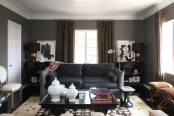 a dark living room with upholstered and leather furniture, dark curtains, some artworks and furniture