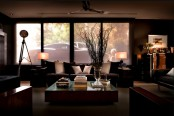 a dark masculine living room with elegant upholstered furniture, a glass coffee table, lamps and a large window