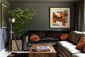 a stylish dark living room with dark walls, an L-shaped sofa, orange pillows and a graphic artwork, a floor lamp and a wooden coffee table