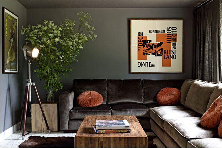 a stylish dark living room with dark walls, an L shaped sofa, orange pillows and a graphic artwork, a floor lamp and a wooden coffee table