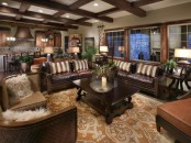 a dark living room with leather furniture, a wooden coffee table, a printed rug and faux fur pillows